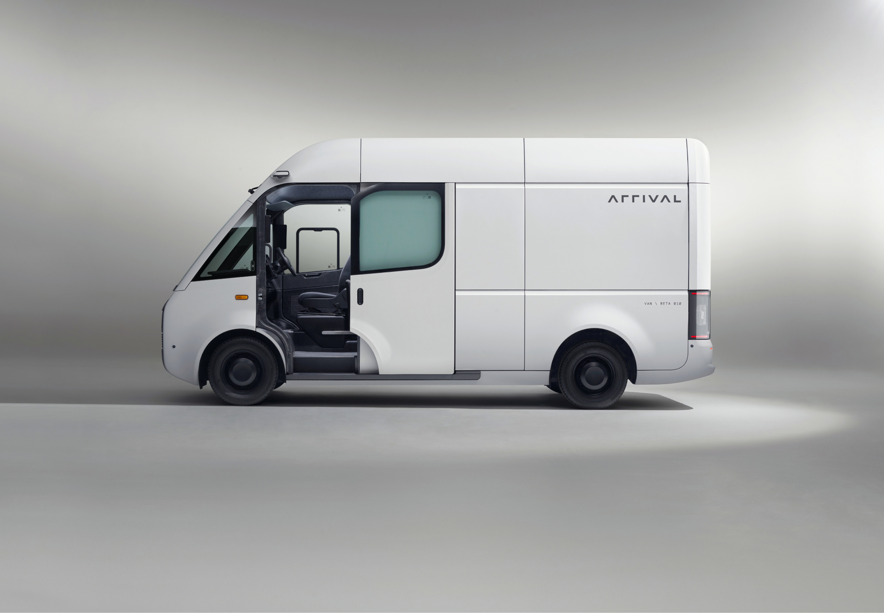 White Arrival Beta Van from side with door closed and light grey background