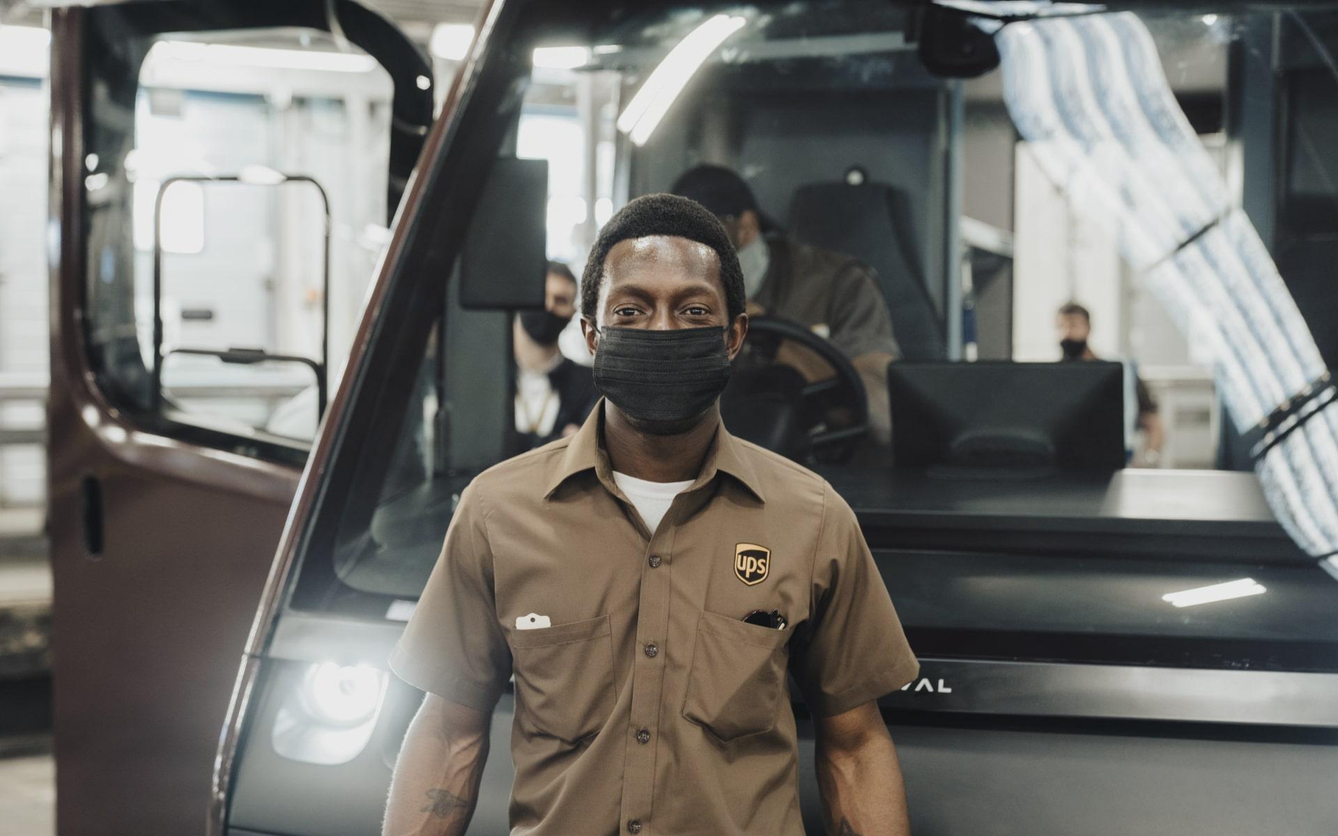 Van driver standing in front of Arrival vehicle